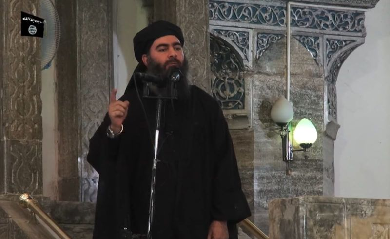 """This July 5, 2014 photo shows an image grab taken from a propaganda video released by al-Furqan Media allegedly showing the leader of the Islamic State (IS) jihadist group, Abu Bakr al-Baghdadi, aka Caliph Ibrahim, adressing Muslim worshippers at a mosque in the militant-held northern Iraqi city of Mosul. Baghdadi, who on June 29 proclaimed a """"caliphate"""" straddling Syria and Iraq, purportedly ordered all Muslims to obey him in the video released on social media. - In early 2014 the self-styled Islamic State entered the northern Syrian city of Raqqa, declaring it their capital and beginning a reign of terror marked by grisly public executions. Armed sharia police patrolled the streets as """"enemies"""" of the regime were crucified or decapitated, their severed heads impaled on spikes in the city square. (Photo by - / AFP)"""