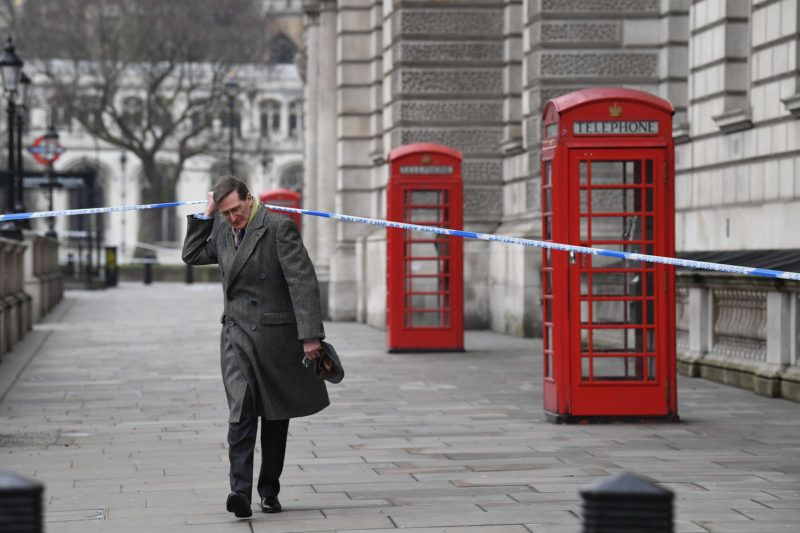 British politician Dominic Grieve lifts the police cordon as he walks along Whitehall in Westminster, central London, on March 23, 2017 a day after a deadly terror attack killed at least three people. - Britain's parliament reopened on Thursday with a minute's silence in a gesture of defiance a day after an attacker sowed terror in the heart of Westminster, killing three people before being shot dead. Sombre-looking lawmakers in a packed House of Commons chamber bowed their heads and police officers also marked the silence standing outside the headquarters of London's Metropolitan Police nearby. (Photo by Justin TALLIS / AFP)
