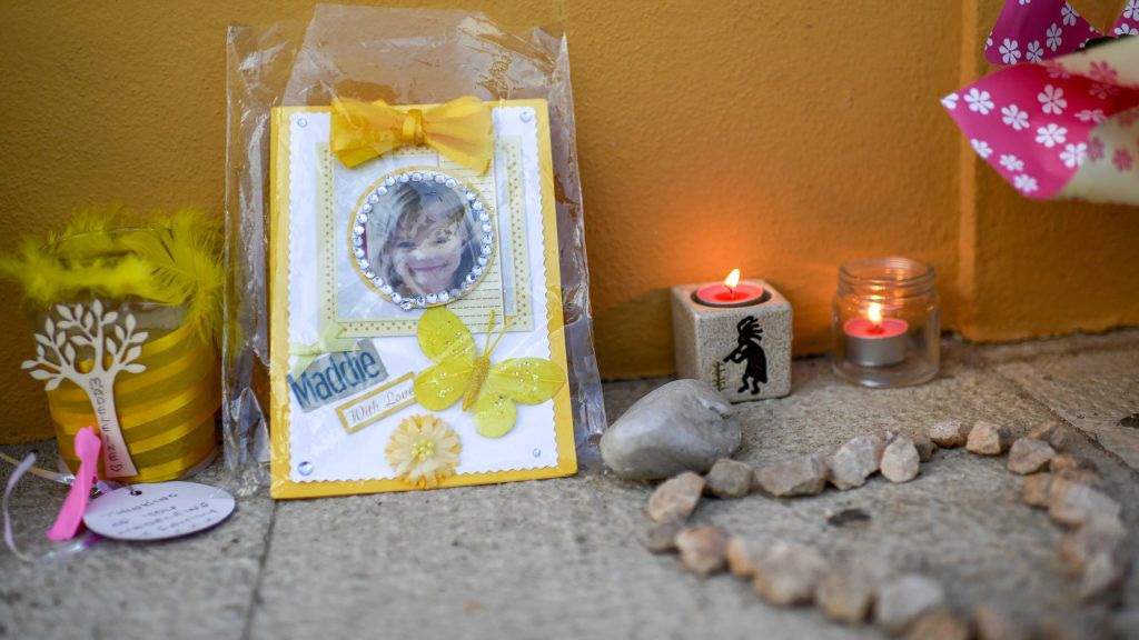 """Picture shows candles and a photograph of """"Maddie"""", placed on the street as a tribute to Madeleine McCann, outside the church in Praia da Luz near Lagos on May 3, 2017. - Madeleine McCann (Maddie) disappeared in Praia da Luz on May 3, 2007. Portuguese police closed the case in 2008 before reopening it five years later. (Photo by FRANCISCO LEONG / AFP)"""