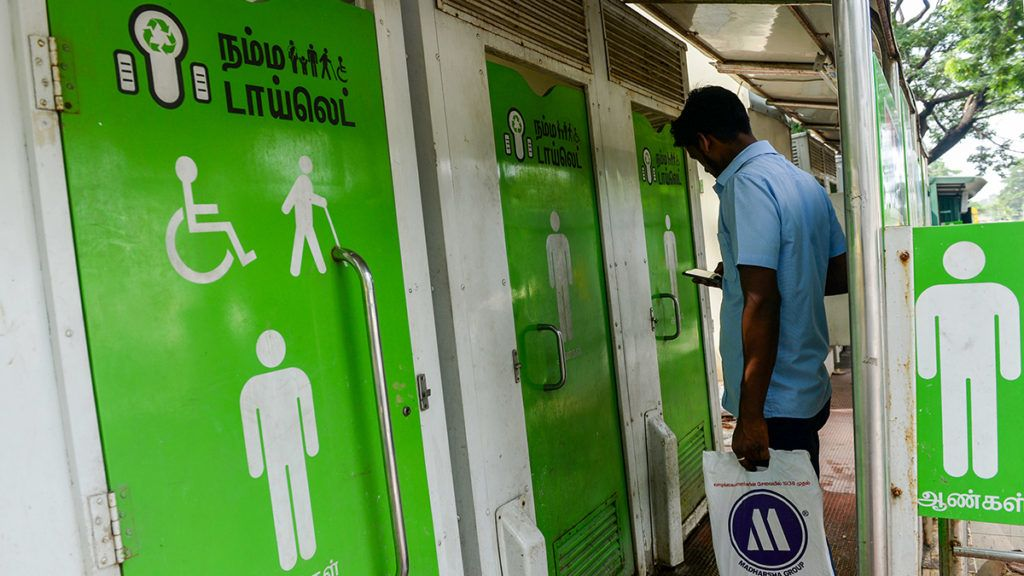 An Indian resident checks his phone as he waits to use a public toilet on a street in  Chennai on November 15, 2017. (Photo by ARUN SANKAR / AFP)
