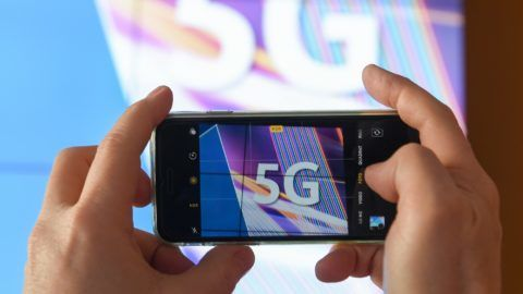 """19 March 2019, Rhineland-Palatinate, Mainz: A journalist photographs the abbreviation """"5G"""" with his smartphone before the start of the auction of 5G mobile radio frequency blocks at the Mainz technology location of the Federal Network Agency. The abbreviation 5G stands for 5th mobile generation. The transfer rate is about 100 times faster than its predecessor 4G, also called LTE. With the auction, the federal government can hope for additional revenues worth billions. Photo: Arne Dedert/dpa"""