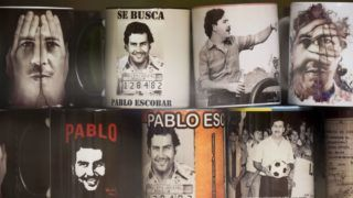 View of souvenirs with the image of the late Colombian drug lord Pablo Escobar for sale in a hairdresser's at Pablo Escobar neighborhood, on November 28, 2018, in Medellin, Colombia. - December 2 marks the 25th anniversary of Escobar's death. (Photo by Raul ARBOLEDA / AFP)