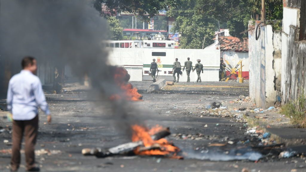 A man stands next to burning tyres near the border between Venezuela and Colombia (background) in Urena as the crossing between both countries remains closed on February 25, 2019. - Venezuela's opposition leader and self-declared president Juan Guaido is in Bogota for talks with allies in the regional Lima Group of countries on measures to compel President Nicolas Maduro to leave office while the European Union on Monday urged countries to avoid any military intervention in Venezuela. (Photo by JUAN BARRETO / AFP)