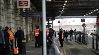 """Security personel stand guard outside Waterloo station in central London on March 5, 2019, following a report of a suspicious package at the station. - Three small improvised explosive devices were found at buildings at Heathrow Airport, London City Airport and Waterloo train station in what the Metropolitan Police Counter Terrorism Command said was being treated as a """"linked series"""". (Photo by Tolga AKMEN / AFP)"""