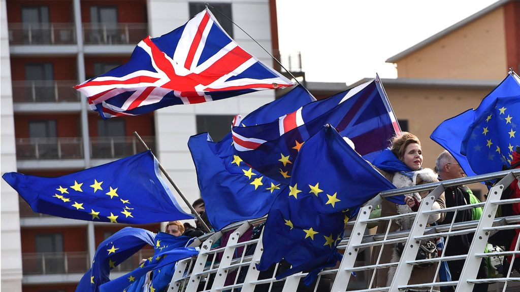 Anti-Brexit activists fly EU and a Union flag from the Millennium Bridge during a demonstration by fishermen on the River Tyne in Newcastle, northeast England on March 15, 2019, against the terms of the current Brexit deal being offered by Britain's Prime Minister Theresa May. - People working in the fishing industry supported by the pro-Brexit Fishing for Leave organisation, launched a flotilla on Friday in protest against the prospect of Britain continuing to adhere to the EU's Common Fisheries Policy that sets quotas and fishing rights during the transition period after Britain has formally left the European Union. (Photo by Andy Buchanan / AFP)