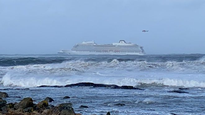 """The cruise ship Viking Sky is pictured on March 23, 2019 near the west coast of Norway at Hustadvika near Romsdal. - Emergency services said on March 23, 2019 they were airlifting 1,300 passengers off a cruise ship off the Norwegian coast. The Viking Sky cruise ship sent an SOS message due to """"engine problems in bad weather"""", southern Norway's rescue centre said on Twitter, while police reported the passengers would be evacuated by helicopter. (Photo by Odd Roar LANGE / NTB Scanpix / AFP) / Norway OUT"""