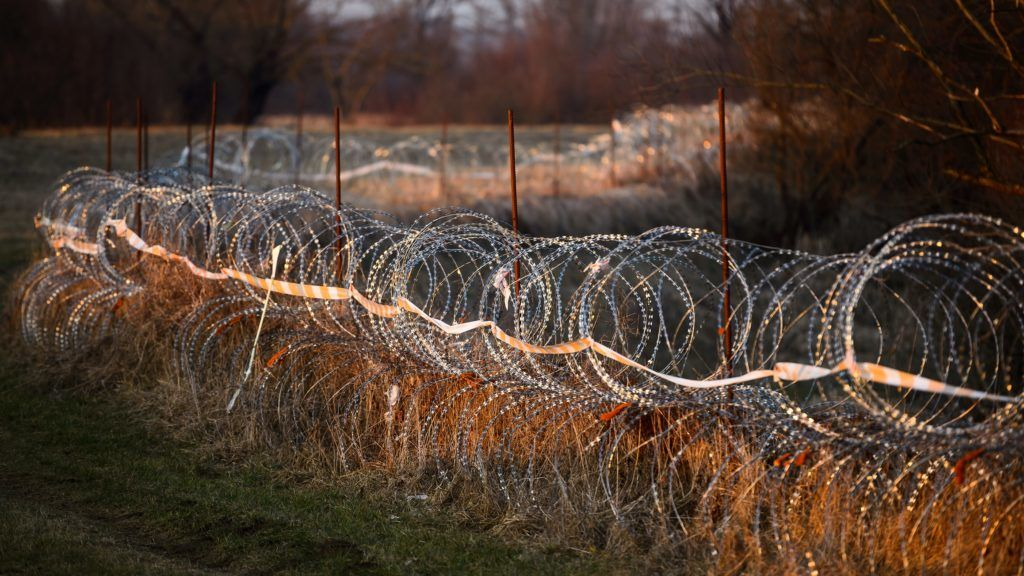 """A barbed wire fence is seen at the Slovenian-Croatian border, near the village of Veliki Obrez, in Slovenia on February 16, 2017. - Slovenia on January 26, 2017 approved a bill allowing police to seal the border with Croatia to migrants in case of a new influx along the so-called Balkan route, sparking condemnation from rights groups. Under the new legislation, Slovenian authorities can reject asylum seekers directly at the frontier with non-Schengen member Croatia if migrant numbers suddenly rise and """"threaten public order and internal security"""". (Photo by Jure MAKOVEC / AFP)"""