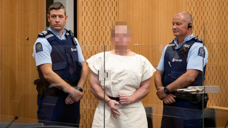 Brenton Harrison Tarrant, a 28-year-old Australian national, appears in New Zealand court on Saturday March 16, 2019, shackled and wearing all-white prison garb, and showed no emotion when the judge read him one murder charge. He was charged with murder for the shooting deaths of at least 49 people during Friday prayers in Christchurch.