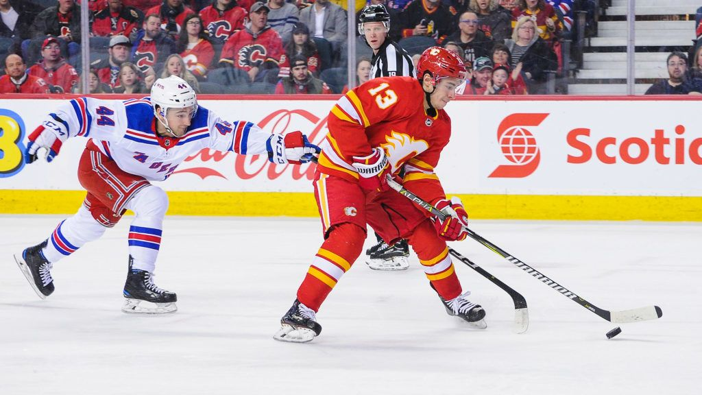 CALGARY, AB - MARCH 15: Johnny Gaudreau #13 of the Calgary Flames skates with the puck past Neal Pionk #44 of the New York Rangers during an NHL game at Scotiabank Saddledome on March 15, 2019 in Calgary, Alberta, Canada.   Derek Leung/Getty Images/AFP