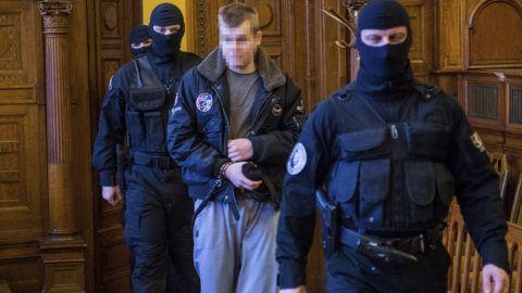 Budapest, 2018. február 5.A 2016. szeptember 24-ei Teréz körúti robbantás vádlottját vezetik be a tárgyalóterembe az ellene előre kitervelten, aljas indokból, több ember és hivatalos személy sérelmére több ember életét veszélyeztetve elkövetett emberölés bűntettének kísérlete és más bűncselekmények miatt indult per második tárgyalási napján a Fővárosi Törvényszéken 2018. február 5-én.MTI Fotó: Balogh Zoltán