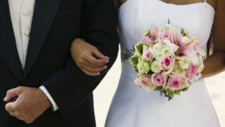 Bride Standing Arm In Arm With Father