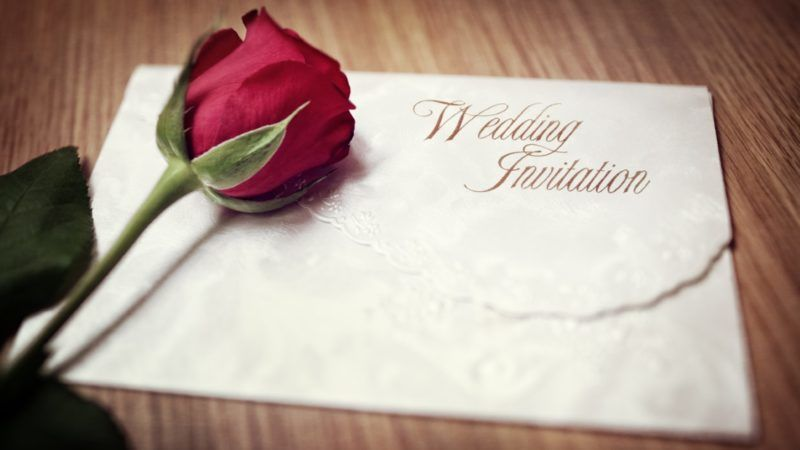 Wedding invitation and red rose on a wooden table