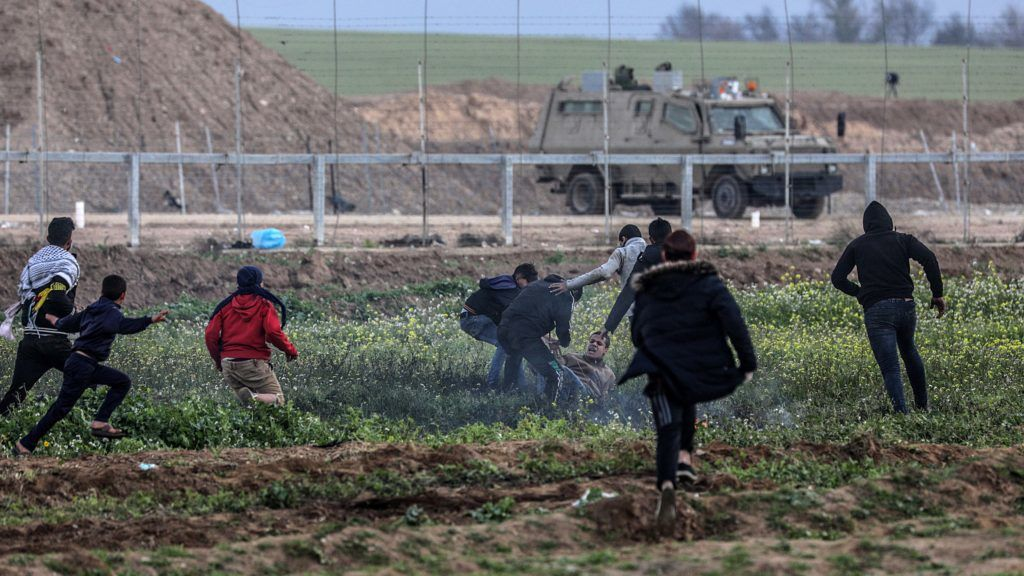 Gáza, 2019. március 1.Palesztin tüntetők sebesült társuk segítségére sietnek az izraeli katonákkal vívott összecsapás alatt a Gázai övezet határkerítésénél 2019. március 1-jén. A Gázai övezetet uraló Hamász radikális iszlamista szervezet 2018. márciusi felhívására a palesztinok péntekenként az izraeli blokád ellen tiltakoznak, azt követelve, hogy visszatérhessenek a földre, ahonnan a zsidó állam 1948-ban történt megalapításakor elűzték őket.MTI/EPA/Mohamed Szaber