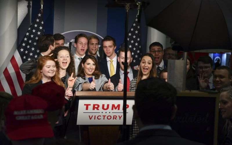 NATIONAL HARBOR, MD - FEBRUARY 28: Ronna McDaniel, Chair of the Republican National Committee, center, poses for photos with conference attendees in a booth that resembles the press room at The White House which was displayed at CPAC 2019 on February 28, 2019 in National Harbor, Md. (Photo by Ricky Carioti/The Washington Post via Getty Images)