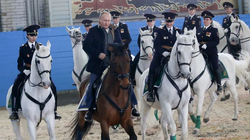 MOSCOW, RUSSIA - MARCH 07: (RUSSIA OUT) Russian President Vladimir Putin (C) rides a horse while visiting the mounted police department on March 7, 2019 in in Moscow, Russia. Putin congratulated female policemen at a police special unit,  with the upcoming International Women's Day. (Photo by Mikhail Svetlov/Getty Images)