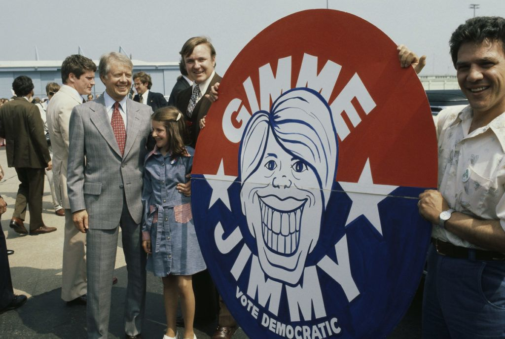 """President Jimmy Carter stands with a girl and two men holding a """"Gimme Jimmy"""" sign during the President's visit to a Chicago airport. (Photo by © Wally McNamee/CORBIS/Corbis via Getty Images)"""