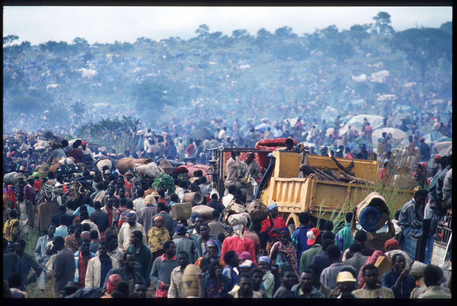 186971 029: A construction truck edges along April 30, 1994 as people file past it in Tanzania. Two hundred fifty thousand refugees cross the border to flee the advance of the Tutsi Rwandese Patriotic Front. The trouble begins when President Habyarimana's plane is shot down near the Kigali airport by members of the government army. (Photo by Scott Peterson/Liaison)