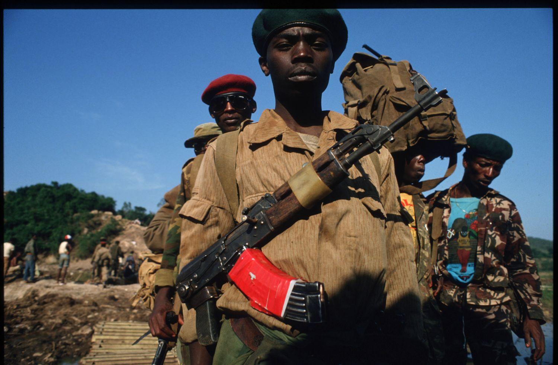 221260 20: Members of Patriotic Front of Rwanda walk across a bridge over the Akanyaru river June 3, 1994 in Rwanda. They are preparing for the final offensive towards Kabyagi and Gitarma. (Photo by Scott Peterson/Liaison)
