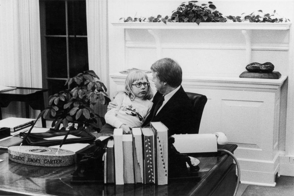 American President JImmy Carter talks with his daughter Amy, who sits on his lap, in the Oval Office of the White House, Washington DC, 1978. (Photo by Katherine Young/Getty Images)