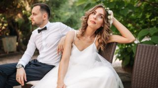 Newlywed coupe sitting on a sofa angry at each other in a middle of an argument. Young couple problem concept outdoor.