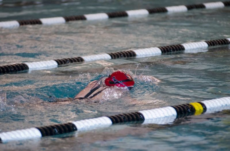 Teenage girl doing the breaststroke in a pool with lane markers during a high school swim meet.