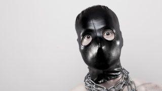 Mann in schwarzer Ganzkopfmaske und Ketten um den Hals