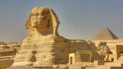 The Great Sphinx of Giza. Monumental limestone statue of a reclining sphinx with a lion's body and a human head (believed to represent the face of the Pharaoh Khephren). One of the pyramids in the background. Giza, Egypt