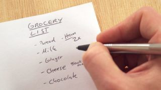 Handwritten grocery list on white note-paper, hand writing with pen