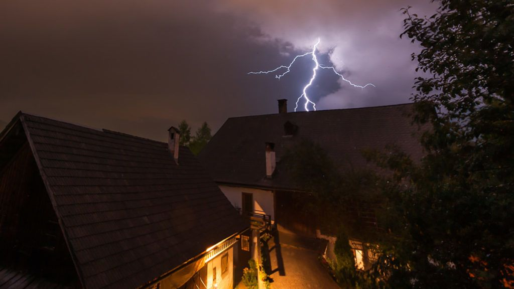 Lightning during a thunderstorm at night behind a farming house in the Austrian alps