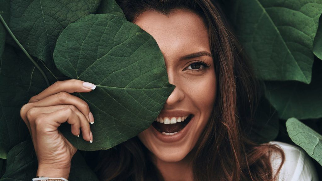 Attractive young woman looking at camera and smiling while standing among the leaves outdoors