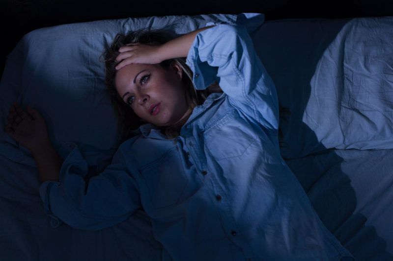 Sleep disorder, insomnia. Young blonde woman lying on the bed awake