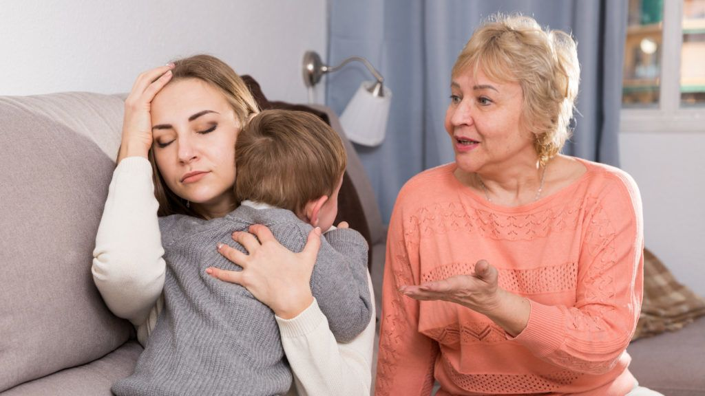 Two adult female are having disagreements with upbringing kid at home.