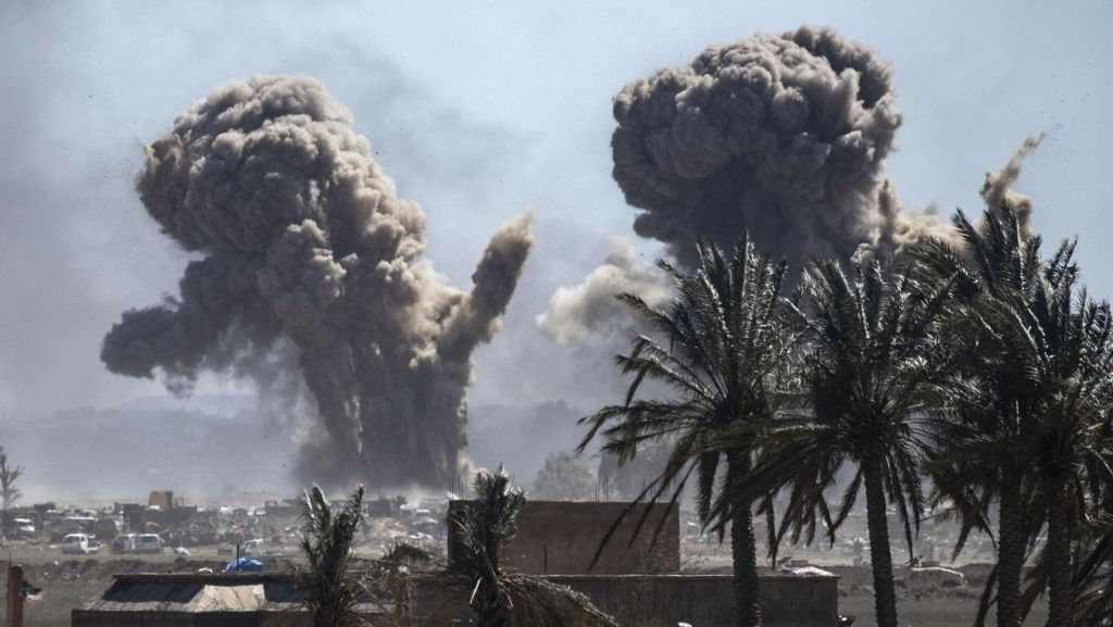 Heavy smoke rises above the Islamic State (IS) group's last remaining position in the village of Baghouz during battles with the Syrian Democratic Forces (SDF), in the countryside of the eastern Syrian province of Deir Ezzor on March 18, 2019. - An air strike pounds a demolished bridge in eastern Syria, sending armed men scampering to hide among the cars and tents of the Islamic State group's smouldering last redoubt. (Photo by Delil SOULEIMAN / AFP)