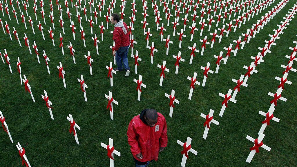 Amszterdam, 2009. december 1.Az AIDS elleni világmozgalmat jelképező piros szalagot viselő fehér kereszteket állítanak fel aktivisták az amszterdami Múzeum téren 2009. december 1-jén, az AIDS elleni küzdelem világnapján. A téren a világnap alkalmából állították fel a kereszteket, hogy emlékeztessenek a betegség áldozataira. (MTI/EPA/Robert Vos)