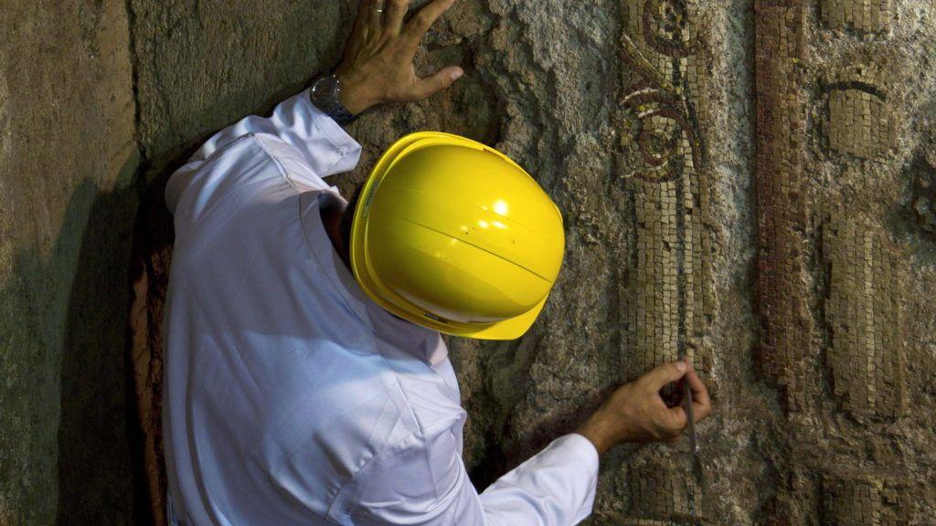 Róma, 2011. július 29. Egy ókori mozaik részletén dolgozik egy régész a római Oppius-domb mélyén. A mozaik egy, valamikor az i. sz. 64 és 109 között épített, 16 méter hosszú és legalább 2 méter magas falat díszített, és feltehetõleg a 98 és 117 között uralkodó Traianus császár fürdõit tartó alagútban állt. A mozaik többek között Apolló meztelen, csak a vállán leplet viselõ, kitharát tartó figuráját és egy múzsát is ábrázol. Régészek feltételezik, hogy a fal akár 8 méter mélységig is lenyúlhat a föld alatt. (MTI/EPA/Massimo Percossi)