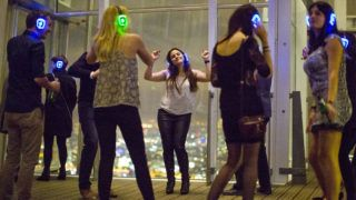 """TO GO WITH AFP STORY BY EDOUARD GUIHAIREDancers attend a 'Silent Disco' in the """"Shard"""" tower on the south bank of the river Thames in central London on November 15, 2014. London's Shard hosts regular Silent Discos, where partygoers don headphones and dance noiselessly to the music they are listening to. Thanks to the headphones, there is no thudding bassline to shout over -- those who are not dancing can talk, laugh and clink glasses as if they were in their own home. AFP PHOTO/JUSTIN TALLIS (Photo by Justin TALLIS / AFP)"""