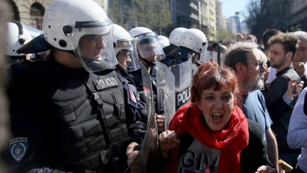 Protesters scuffle with police forces during a demonstration against Serbian President Aleksandar Vucic outside the presidential building in Belgrade, on March 17, 2019. - Opposition supporters gathered outside the presidential building during a press conference of Serbian President Aleksandar Vucic, a day after opponents broke into the state-run RTS television building, demanding to address the population, in images aired live. There have been weekly opposition protests since December against what they describe as Vucic's slide towards autocratic rule, while accusing RTS of pandering to the ruling party and demanding more airtime for opposing views. (Photo by Oliver BUNIC / AFP)
