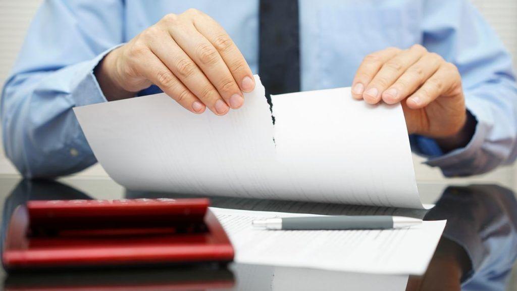 businessman tears document in office