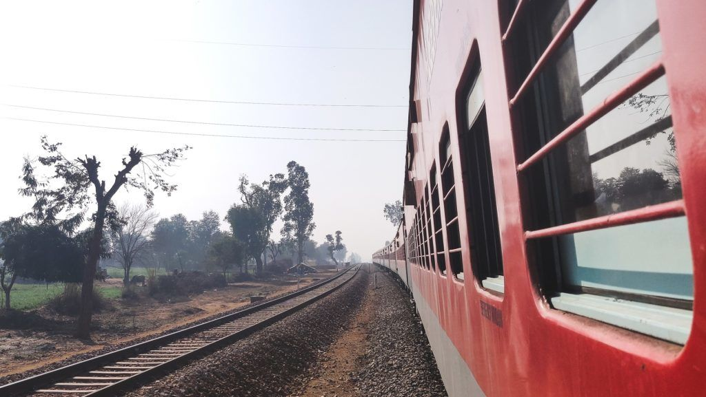 Looking out of the window of a express train of Indian railways with a view of green farm lands. Train is also seen taking a turn.