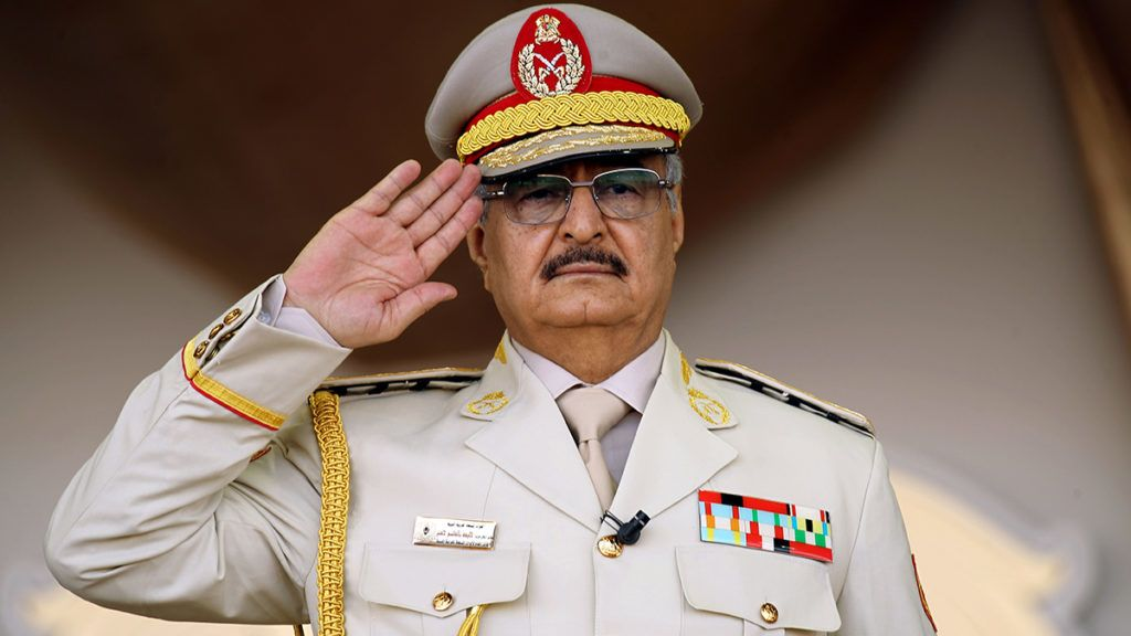 """(FILES) In this file photo taken on May 07, 2018 Libyan Strongman Khalifa Haftar salutes during a military parade in the eastern city of Benghazi during which he announced a military offensives to take from """"terrorists"""" the city of Derna, the only part of eastern Libya outside his forces' control. - Forces loyal to Libyan strongman Khalifa Haftar were pushed back on April 5, 2019 from a key checkpoint less than 30 kilometres (18 miles) from Tripoli, checking their lightning advance on the capital, a security source said. (Photo by Abdullah DOMA / AFP)"""