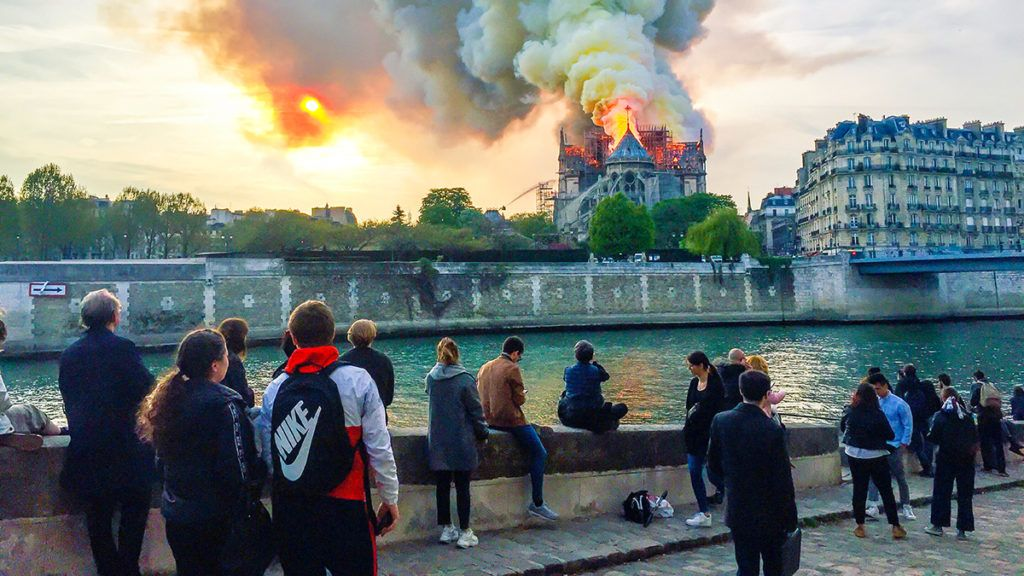 Bystanders look on as flames and smoke billow from the roof at Notre-Dame Cathedral in Paris on April 15, 2019. - A fire broke out at the landmark Notre-Dame Cathedral in central Paris, potentially involving renovation works being carried out at the site, the fire service said.Images posted on social media showed flames and huge clouds of smoke billowing above the roof of the gothic cathedral, the most visited historic monument in Europe. (Photo by Fouad Maghrane / AFP)
