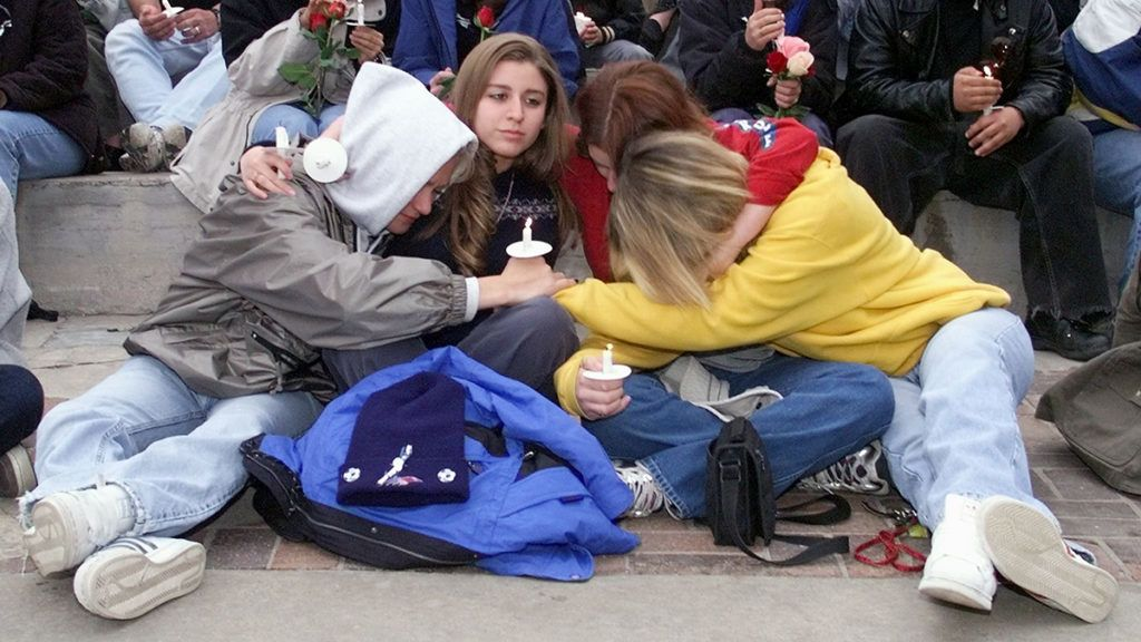 (FILES) In this file photo taken on April 21, 1999 Denver area residents comfort one another during a candle light vigil at Civic Center Park in Denver, CO, held in honor of the students and one teacher killed at Columbine High School in Littleton, CO on  April 20, 1999, when two former students opened fire on their classmates during a suicide mission. - This year marks the 20th anniversary of the Columbine High School shooting, when two youths aged 17 and 18 armed with guns and home-made bombs killed 12 students and a teacher at Columbine high school in Littleton, Colorado before they both committed suicide. (Photo by JEFF HAYNES / AFP)