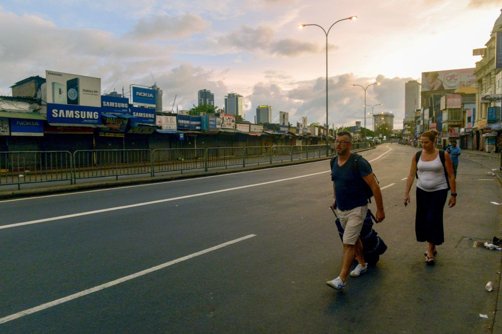 Tourists walk along the road after the Sri Lanka Police curfew in Colombo on April 21, 2019. - A series of eight devastating bomb blasts ripped through high-end hotels and churches holding Easter services in Sri Lanka on April 21, killing at least 207 people, including dozens of foreigners. (Photo by ISHARA S. KODIKARA / AFP)