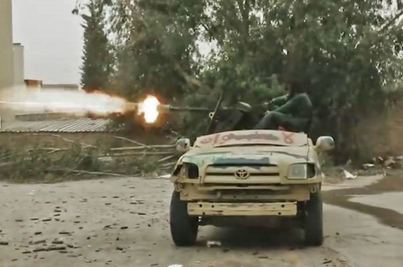 """This grab obtained from a video published on the Libyan strongman Khalifa Haftar's self-proclaimed Libyan National Army (LNA) War Information Division's Facebook page on April 24, 2019, shows a technical (pickup truck mounted with a turret) firing reportedly during clashes with forces loyal to Libya's UN-recognised Government of National Accord (GNA) on the outskirts of the capital Tripoli. (Photo by - / LNA War Information Division / AFP) / RESTRICTED TO EDITORIAL USE - MANDATORY CREDIT """"AFP PHOTO / LNA WAR INFORMATION DIVISION"""" - NO MARKETING NO ADVERTISING CAMPAIGNS - DISTRIBUTED AS A SERVICE TO CLIENTS"""