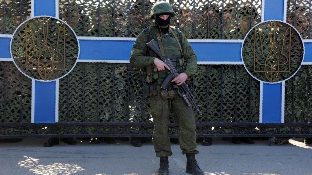 Ukrainian soldier stands behind a fence while unidentified armed men block the headquarters of the Ukrainian Navy in Sevastopol on March 3, 2014. The Russian Black Sea Fleet commander Aleksandr Vitko has issued an ultimatum to the Ukrainian military personnel in Crimea, the Interfax-Ukraine news agency reported. Ukraine accused Russia on Monday of pouring more troops into Crimea as world leaders grappled with Europe's worst standoff since the Cold War and the Moscow market plunged on fears of an all-out conflict. AFP PHOTO/ VIKTOR DRACHEV (Photo by VIKTOR DRACHEV / AFP)