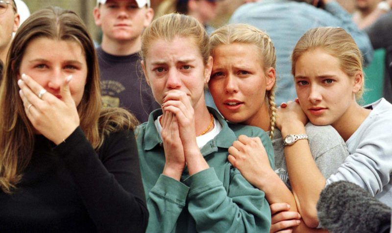 Students from Columbine High School in Littleton, CO watch as the last of their fellow students are evacuated from the school building 20 April 1999 following a shooting spree at the school, which police feared killed as many as 25 people. Two masked teens stormed their school and blasted fellow students with guns and explosives before turning their weapons on themselves in the rampage.   AFP PHOTO     Mark LEFFINGWELL (Photo by MARK LEFFINGWELL / BOULDER DAILY CAMERA / AFP)