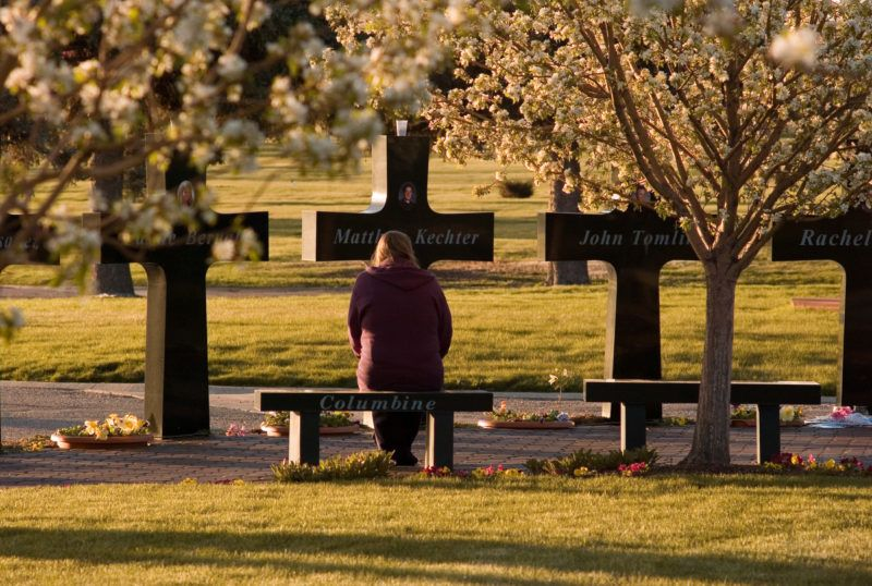 An unidentified mourner pauses at a memorial that stands around the graves of three of the Columbine High School shooting victims at Chapel Hill Memorial Gardens 20 April 2007 in Littleton, Colorado. Friday 20 April marks the eighth anniversary of the Columbine shootings, which were surpassed in magnitude earlier in the week at Virginia Tech when Cho Seung-Hui, a 23-year-old South Korean undergraduate student, killed 33 people including himself.  Kevin Moloney/Getty Images/AFP   =FOR NEWSPAPER, INTERNET, TELCOS AND TELEVISION USE ONLY=