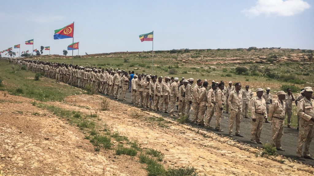 Eritrean soldiers wait in a line on September 11, 2018 to cross the border to attend the border reopening ceremony with Ethiopians as two land border crossings between Ethiopia and Eritrea were reopened for the first time in 20 years in Serha, Eritrea. - diplomacy border trade (Photo by Stringer / AFP)