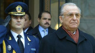 Picture taken on December 21, 2004 shows then outgoing President of Romania, Ion Iliescu (R) attending an official cermony as Iliescu leaves the Cotroceni Palace, the Romanian presidency headquarters in Bucharest. - Romania's former president Ion Iliescu has been indicted for crimes against humanity for his role in the deadly aftermath of the 1989 revolution that toppled the country's communist regime, prosecutors said on Friday, December 21, 2018. (Photo by DANIEL MIHAILESCU / AFP)