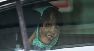 Vietnamese national Doan Thi Huong (R) smiles as she is escorted by Malaysian police out of the High Court in Shah Alam on April 1, 2019. - A Vietnamese woman accused of assassinating the North Korean leader's half-brother will walk free in May after pleading guilty to a lesser charge, her lawyer said. (Photo by Mohd RASFAN / AFP)